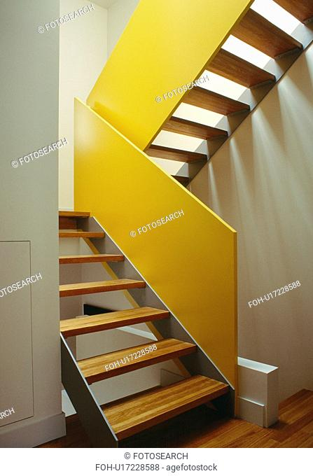 Open-tread staircase with yellow walls
