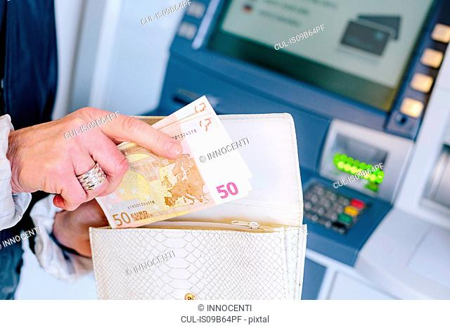 Close up of woman's hands inserting 50 euro notes into purse from cash machine