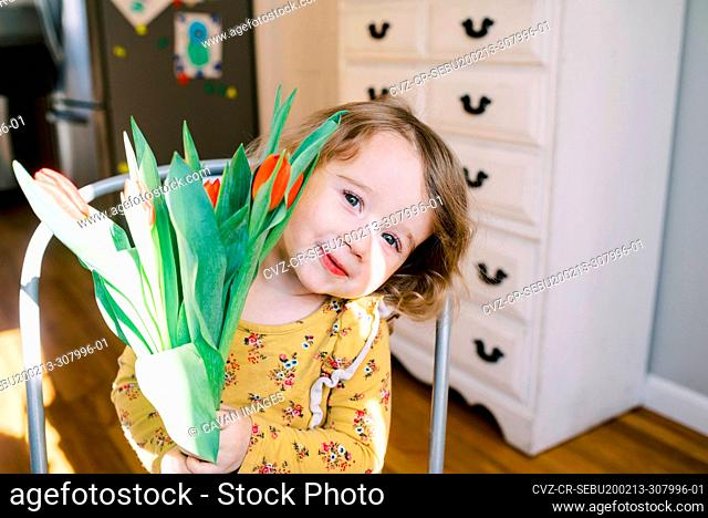 Little two year old girl holding a bunch of tulips