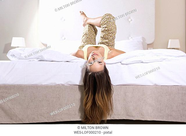 Young woman lying head first on hotel bed