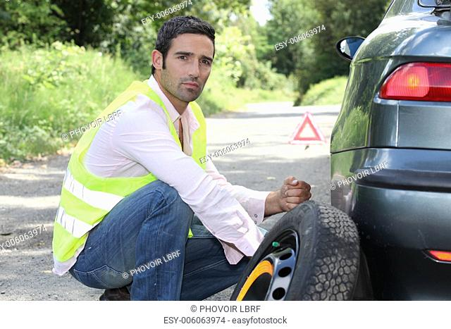 Man changing a tyre at the side of the road