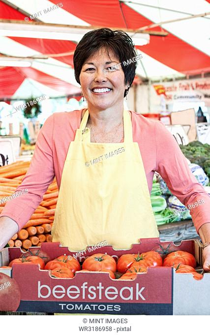 Smiling woman wearing apron holding large tray of fresh tomatoes at a fruit and vegetable market