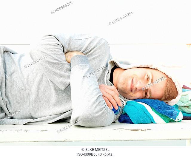 Man lying on beach, Melbourne, Victoria, Australia, Oceania