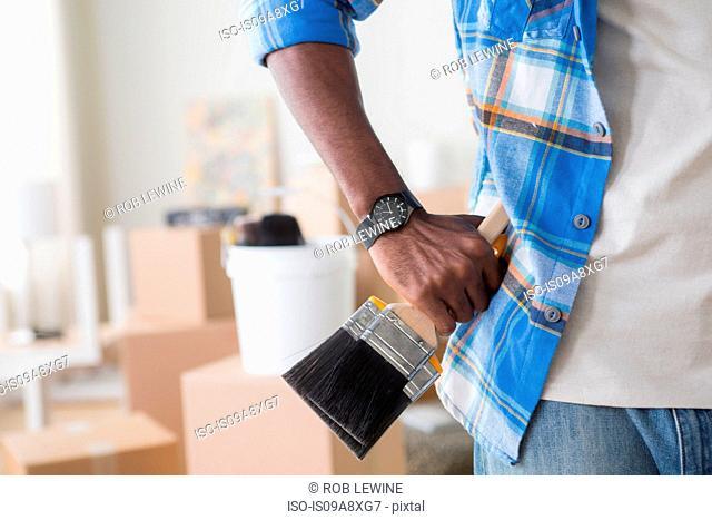 Close-up of man holding paintbrush