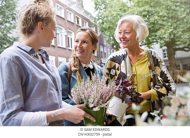 Florist showing plants to mother and daughter at storefront