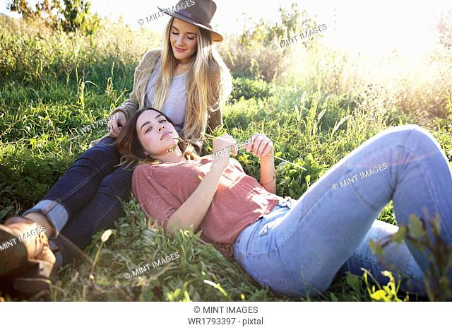 An apple orchard in Utah. Two women lying in the grass