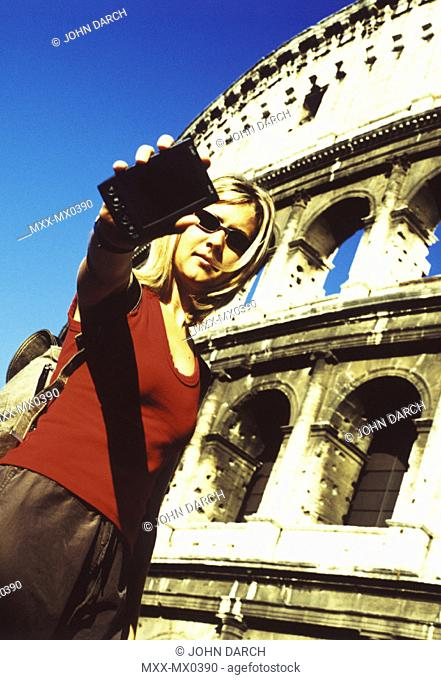 Blonde woman presenting palm pilot in front of the Coliseum, Rome, Italy