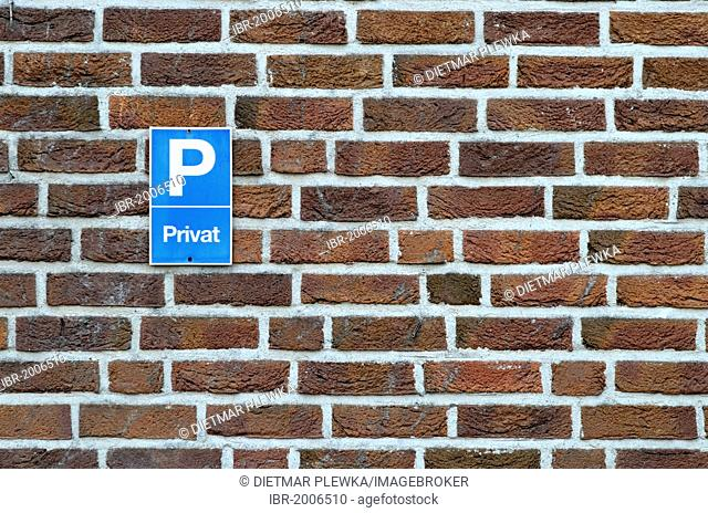 Private car park sign on a brick wall