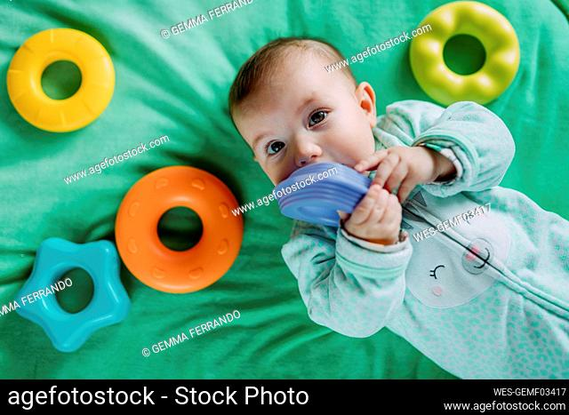 Portrait of baby girl lying on a mat playing with plastic toys