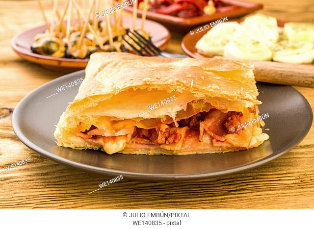 serving homemade puff pastry pie stuffed with cheese and bacon cooked ham