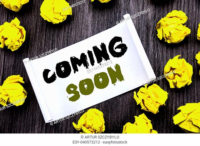 Writing text showing Coming Soon. Business concept for Under Construction Written on sticky note notepad notebook book wooden background with yellow sticky...