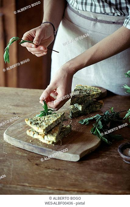 Young woman garnishing homemade chickpea and herb cake