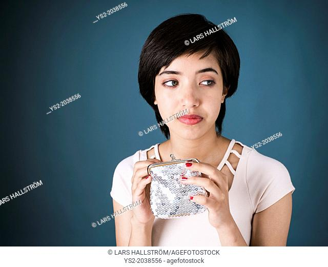Portrait of sad young multiracial woman looking in empty silver wallet