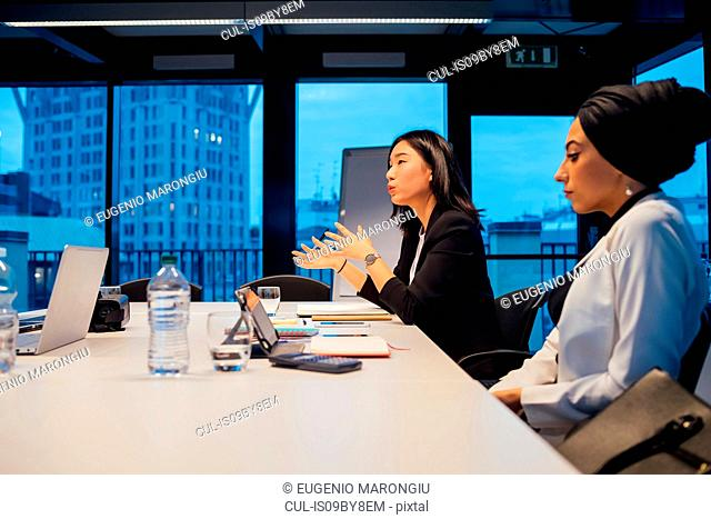 Businesswomen explaining during conference table meeting