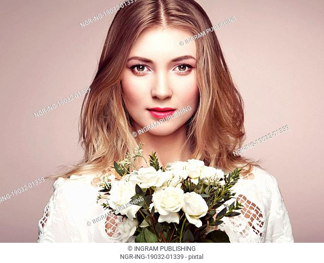 Portrait of beautiful sensual woman with elegant hairstyle. Perfect makeup. Blonde girl. Beauty fashion. Flowers