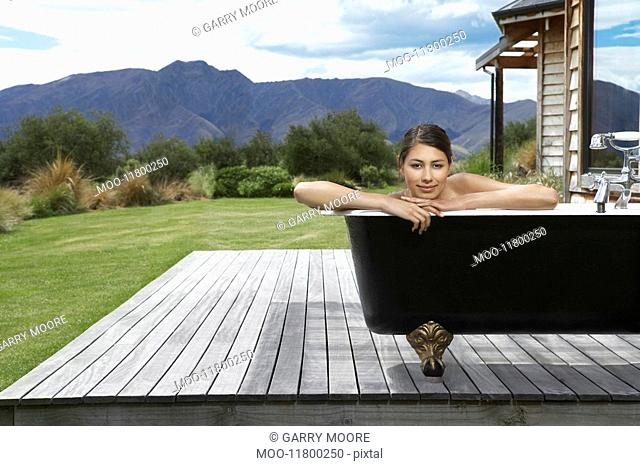 Woman taking bath on porch near mountains