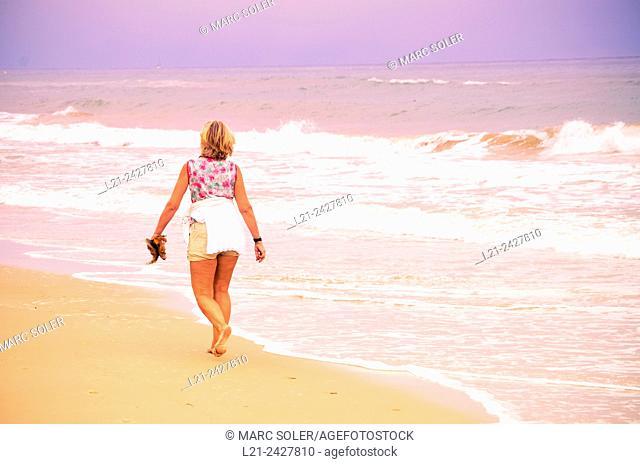 Mature woman walking on the beach. Walking back, blonde, shorts and barefoot. Costa Daurada, Costa Dorada, Catalonia, Spain