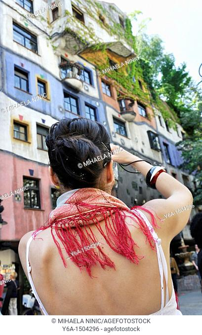 Young woman photographing Hundertwasser House, Vienna, Austria