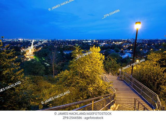 Looking towards the City of Hamilton from a metal stairway that leads up the Niagara Escarpment to the Escarpment Rail Trail in Hamilton, Ontario, Canada