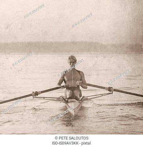 Teenage boy in sculling boat on water