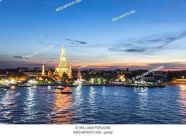 Thailand, Bangkok, Wat Arun temple at dusk with Chao Phraya river on foreground