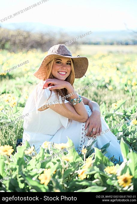 Happy Young Woman Sitting in Flowers with White Dress and Casual Hat