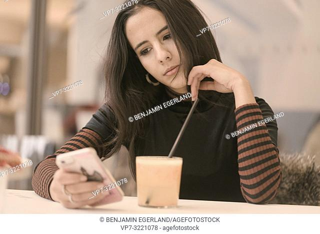 portrait of playful woman using phone while taking a break with healthy juice glass at table in café, in Munich, Germany