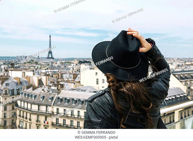 France, Paris, back view of woman at viewpoint wearing a black hat
