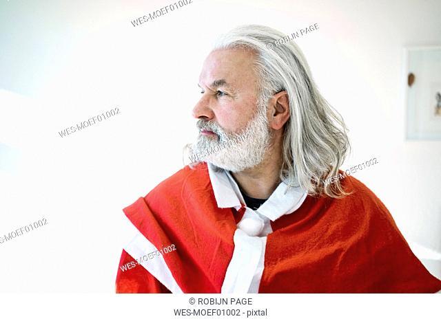 Bearded mature man wearing Santa costume looking sdeways