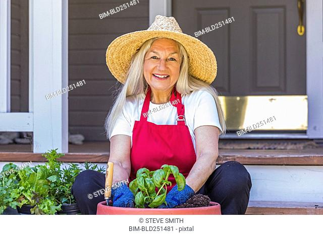 Caucasian woman planting seedling on front stoop