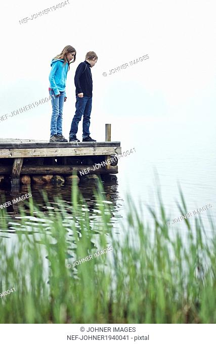 Boy and girl on jetty looking at water, Okno, Smiland, Sweden