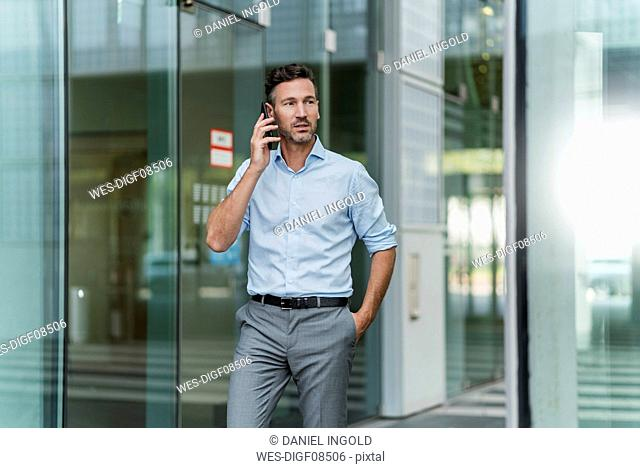 Businessman on the phone outside building