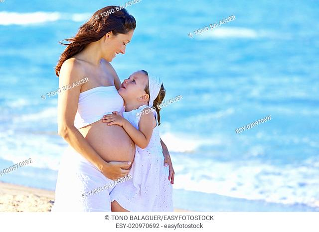 Pregnant mother and daughter on the beach together hug
