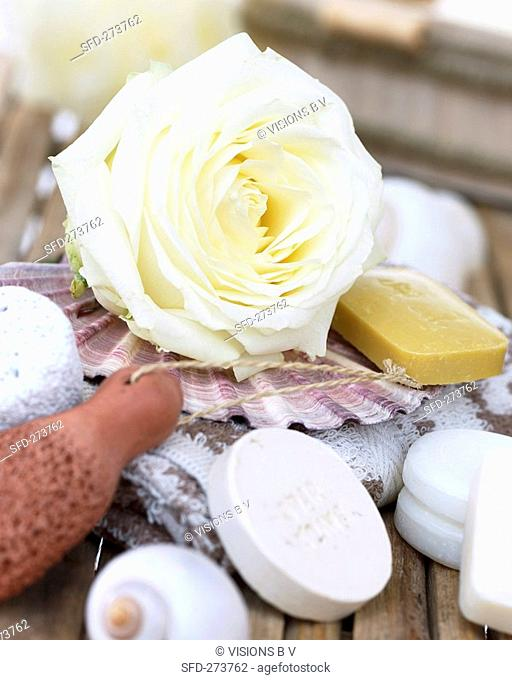 White rose and perfumed soaps on towel