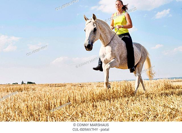 Woman riding grey horse bareback in field