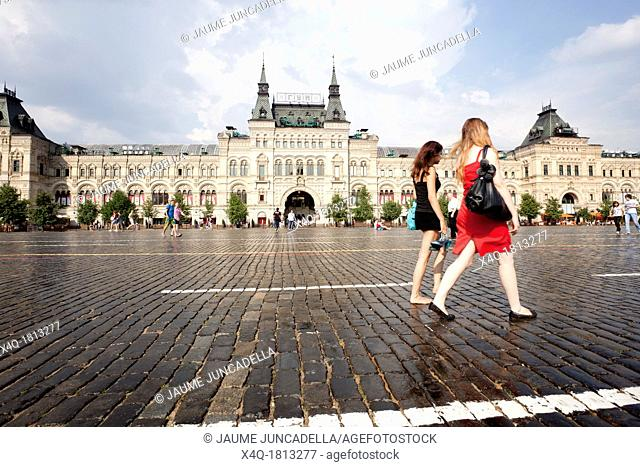 Two girls walking through the Red Square in front of the GUM