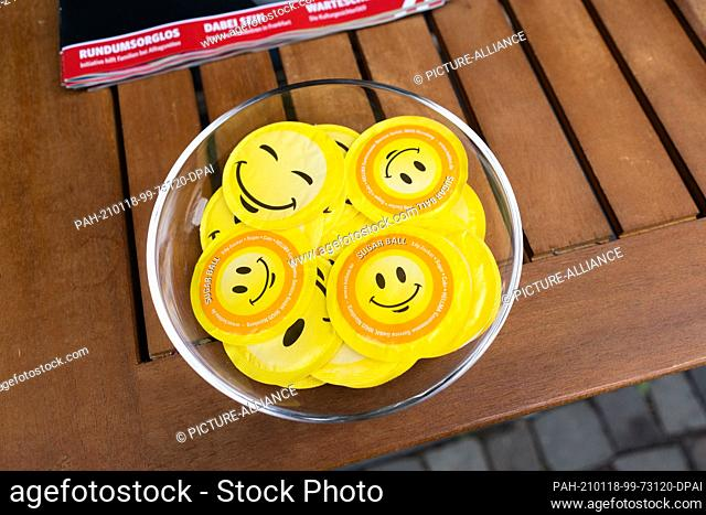 18 January 2021, Hessen, Oberursel: In the pedestrian zone of the town on the edge of the Taunus, free sugar packets with smiley faces printed on them