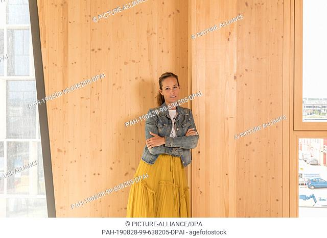 """27 August 2019, Austria, Wien: Caroline Palfy, master builder, engineer and project developer, leans against a wooden wall inside the new """"""""Hoho Wien"""""""""""
