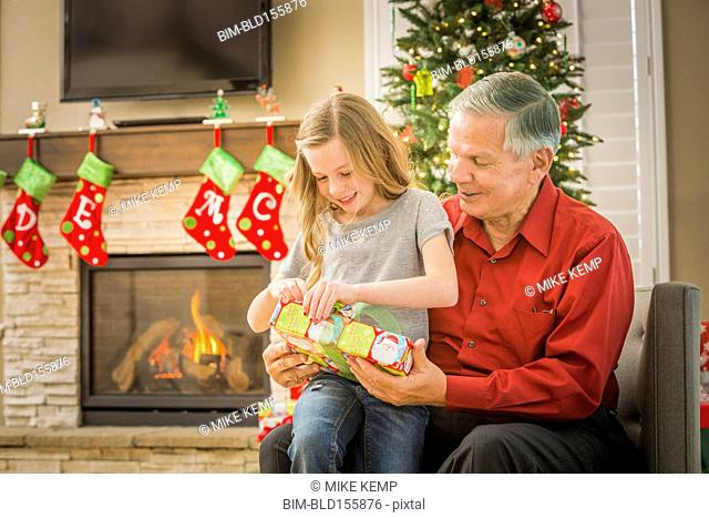 Caucasian grandfather opening Christmas gifts with granddaughter
