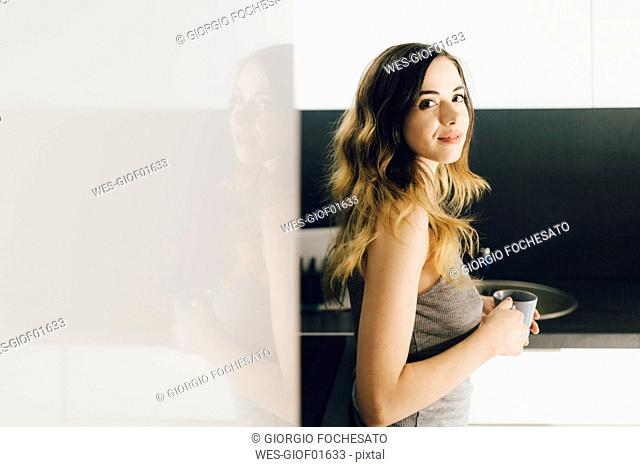 Smiling young woman drinking coffee in kitchen