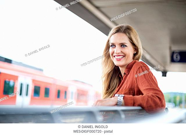 Portrait of smiling young woman sitting at platform