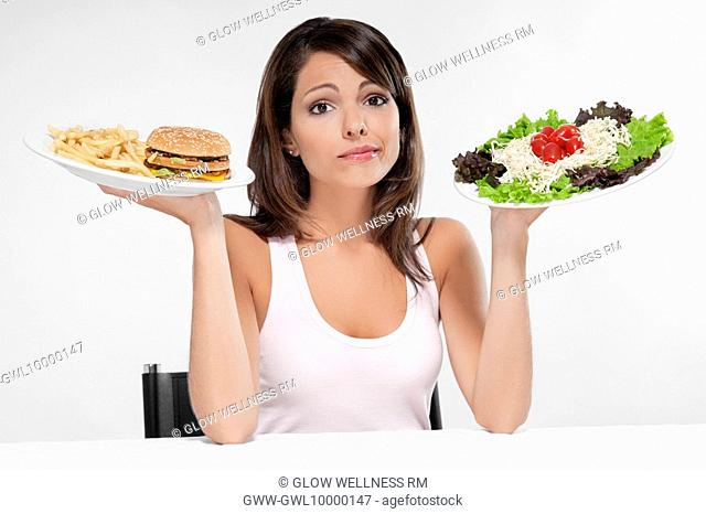 Woman choosing between a hamburger and salad