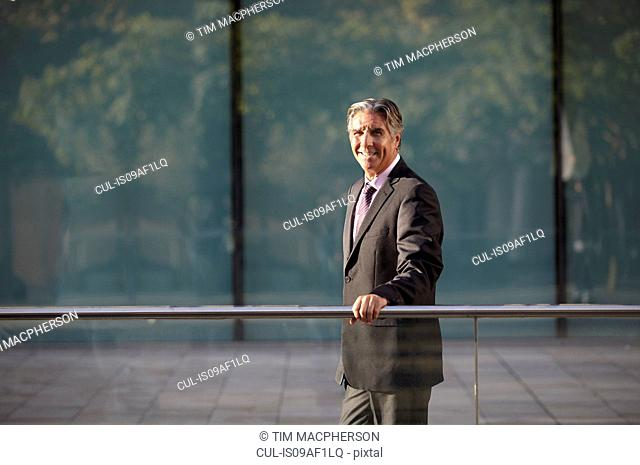 Businessman holding railing