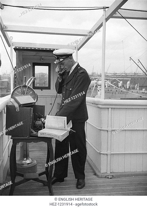 A ship's officer on the bridge uses a portable telephone connected to a land line, c1945-c1965. His telephone directory is stamped, 'Its quicker by rail