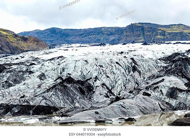 travel to Iceland - tourists on surface of Solheimajokull glacier (South glacial tongue of Myrdalsjokull ice cap) in Katla Geopark on Icelandic Atlantic South...