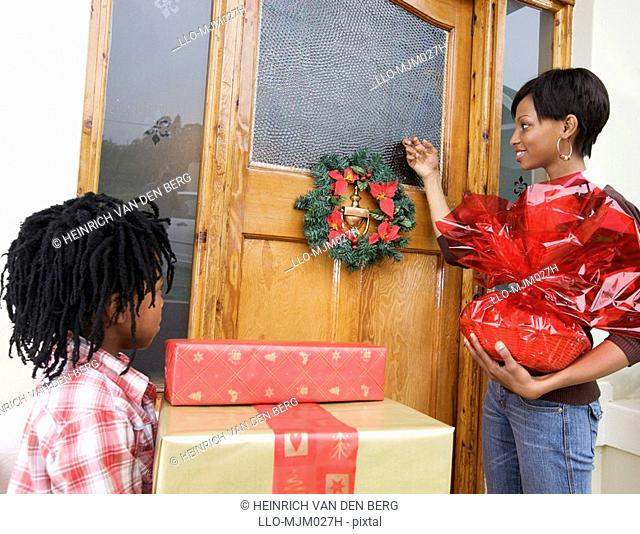 Mother and son in front of door during Christmas time, Pietermaritzburg, KwaZulu-Natal Province, South Africa