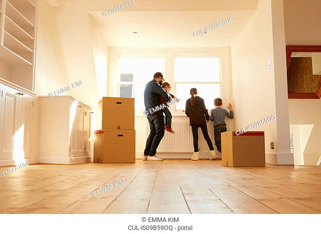 Mid adult man and three children looking from window of new home