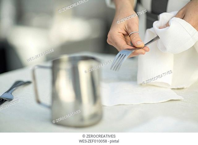 Close-up of waitress preparing dining table in restaurant