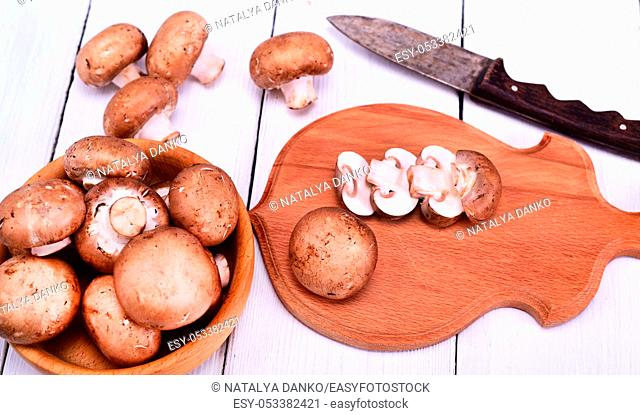 fresh mushrooms champignons on a brown wooden cutting board and in a wooden bowl on a white background