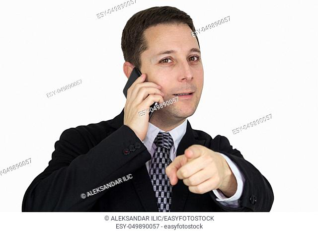 Businessman in Black Suit Talking On The Phone And Pointing Index Finger Towards Camera Against White Background